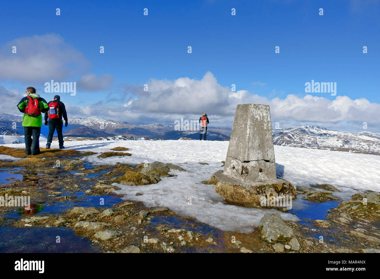 Hill walkers at the summit trig point of Ben Led in theTrossachs of Scotland - Stock Image