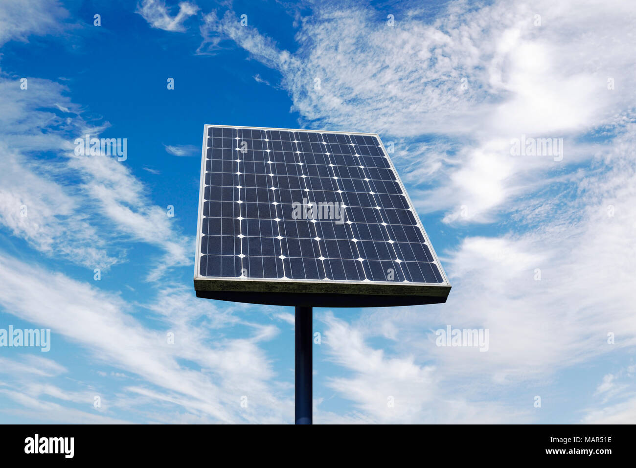 Small Solar Panel Against a Cloudy Blue Sky - Stock Image
