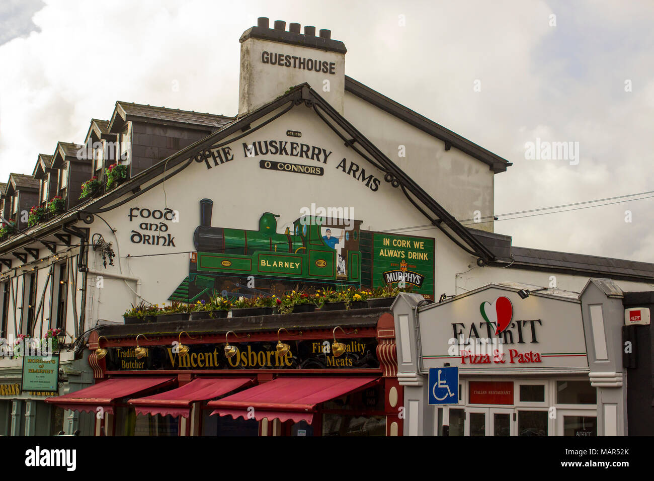 Blarney County Cork Ireland The signage on the gable wall of the Muskerry Arms a traditional Irish Pub on the main street of the town - Stock Image