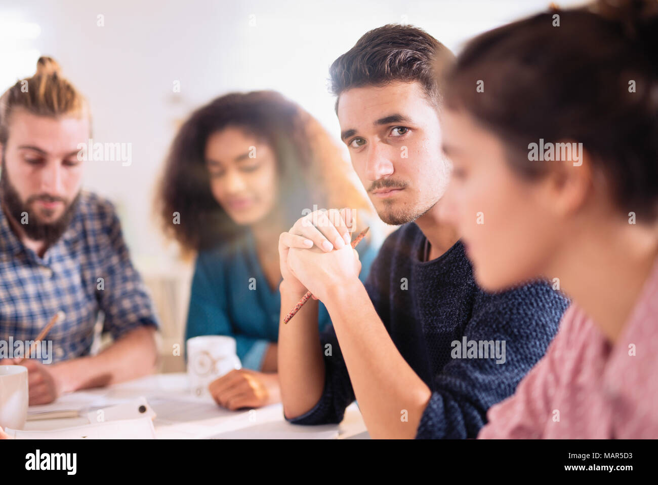 young man looking at the camera during a work meet - Stock Image