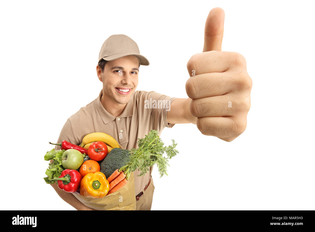 Delivery man with a bag of groceries making a thumb up gesture isolated on white background - Stock Image