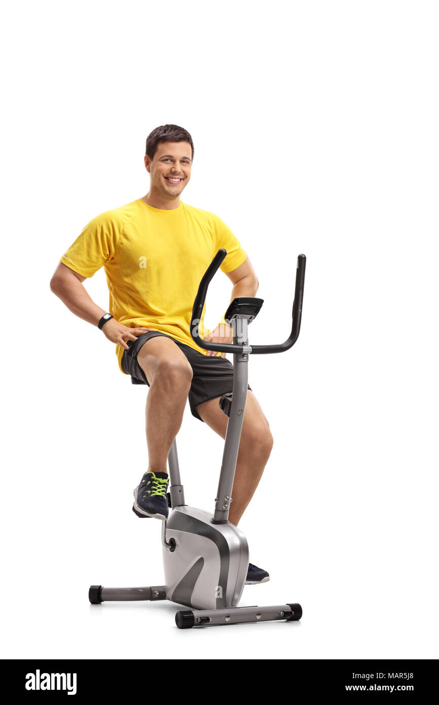 Young man working out on stationary bike isolated on white background - Stock Image
