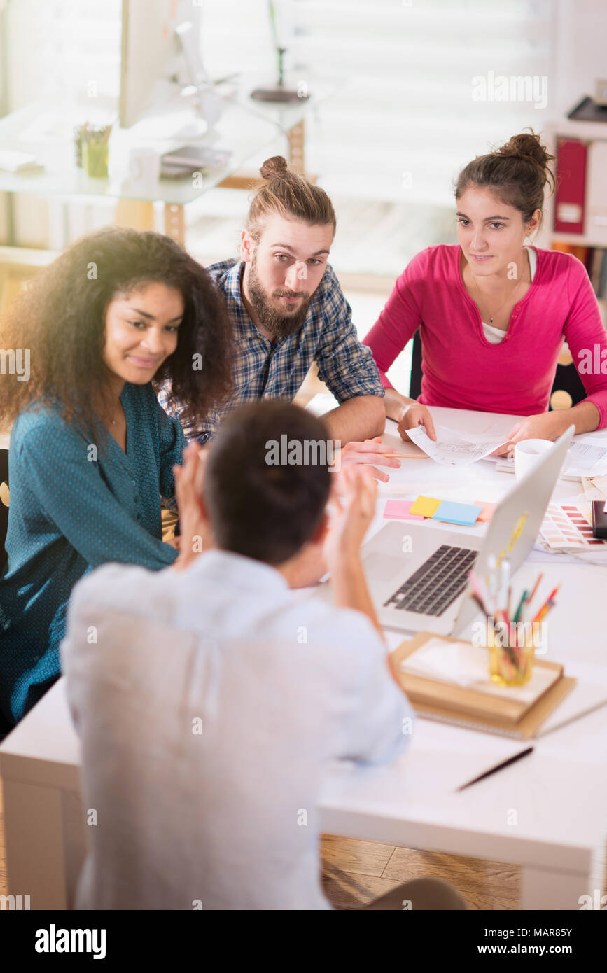 Young colleagues share ideas in front of a laptop.New project - Stock Image