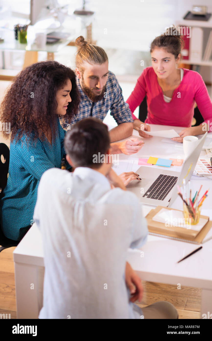 At office. Meeting around a table, a young multiethnic team shar - Stock Image