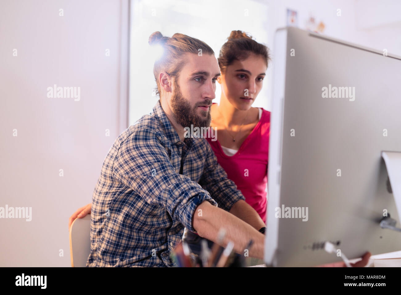 office, two young colleagues, a man and a woman, discuss a project - Stock Image