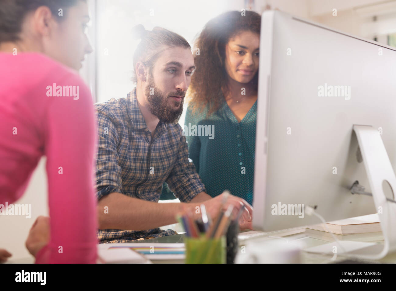 Working meeting in front of the computer to share ideas on project - Stock Image