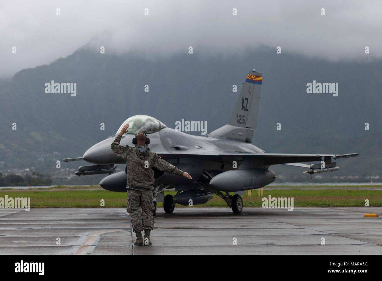 A U S  Airman guides an F-16 Fighting Falcon fighter jet assigned to