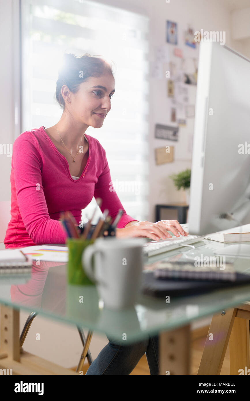 Beautiful young woman sitting at her desk in front of computer Stock Photo