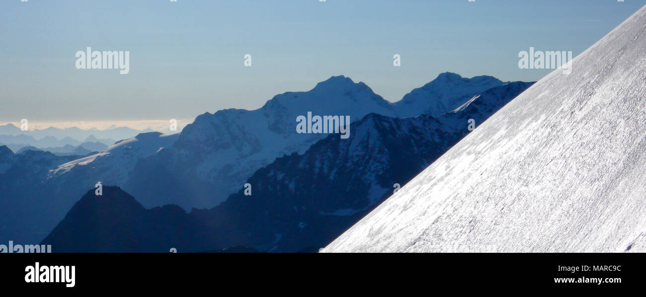 fantastic mountain landscape panorama with a glistening snow slope in the foreground and many silhouette ridges behind - Stock Image