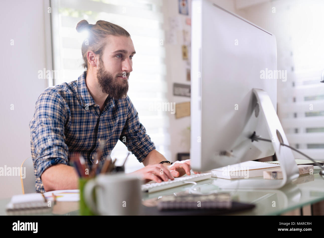 Young man sitting at his desk in front of his computer  - Stock Image