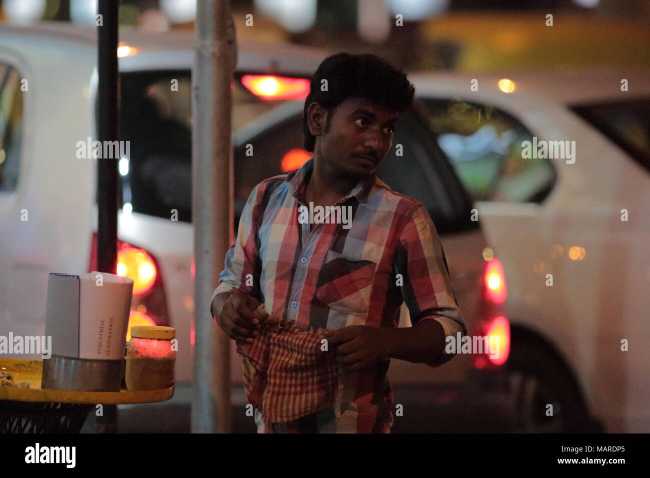 Bangalore, India - October 16, 2016: An unknown street side vendor, stands looking for customers this evening at MG Road, Bangalore. - Stock Image