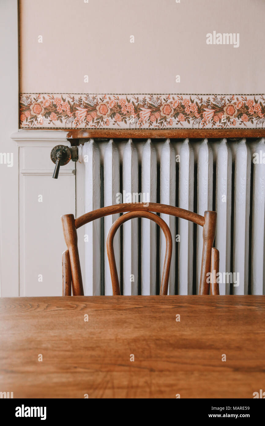 Details of an elegant french dining room with wooden antique furniture and flower pastel wallpaper, rib radiator - Stock Image