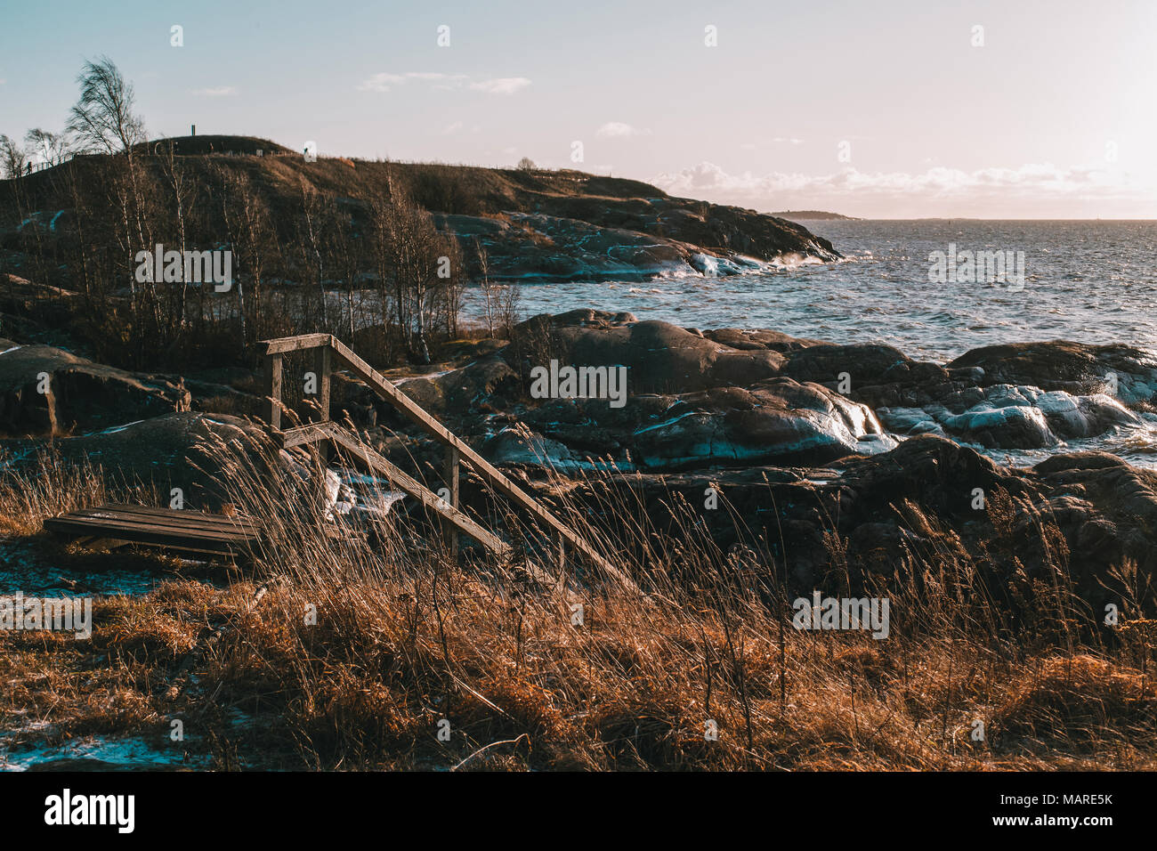 Wooden stairs by the rocky seacoast of Suomelinna island during a windy winter afternoon, Helsinki - Finland - Stock Image