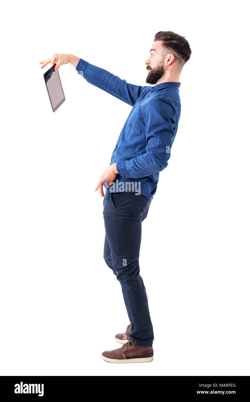 Shocked bearded businessman holding tablet with two fingers. Displeased concept. Full body isolated on white background. - Stock Image
