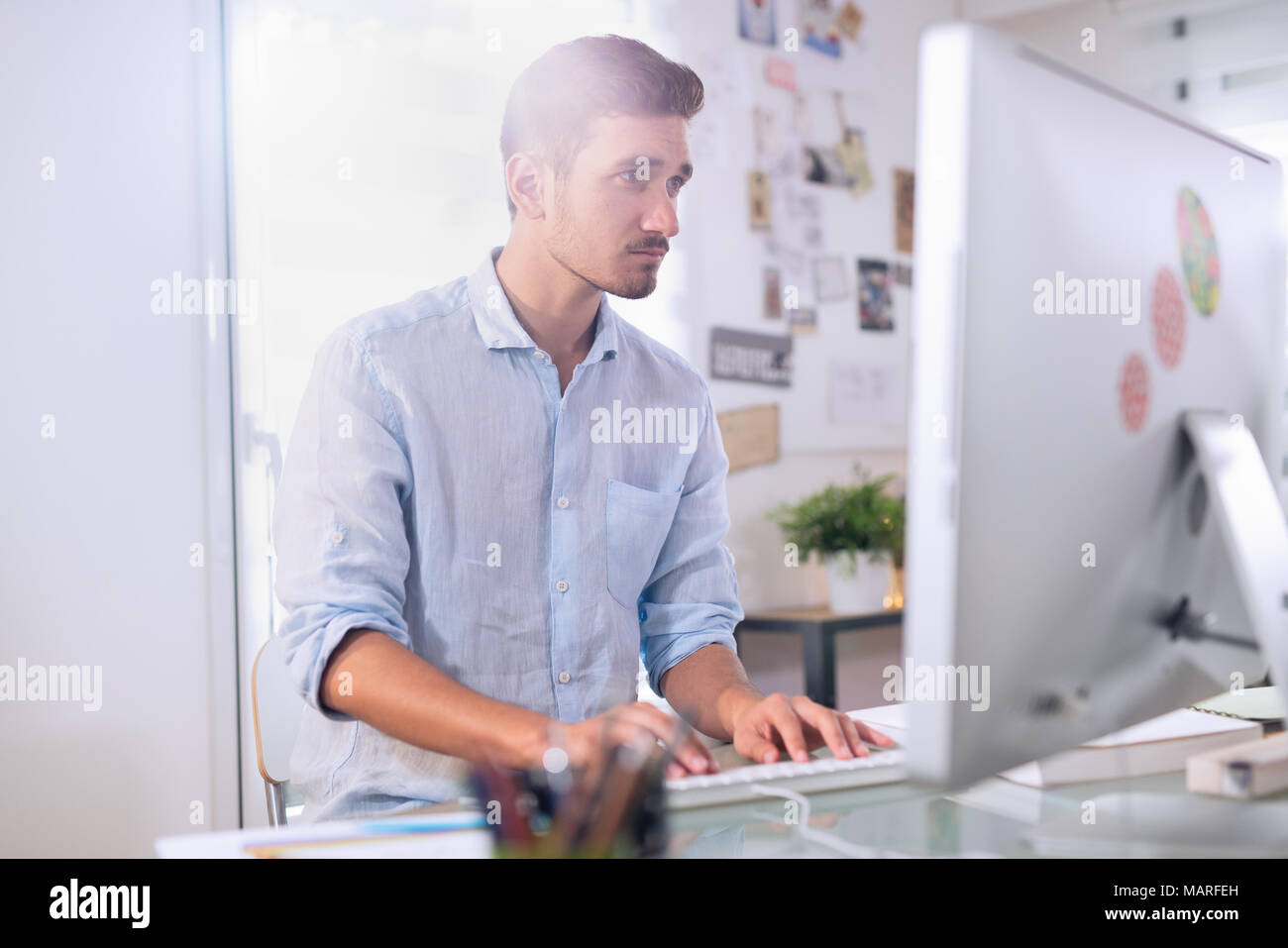 a man sitting in front of his computer - Stock Image