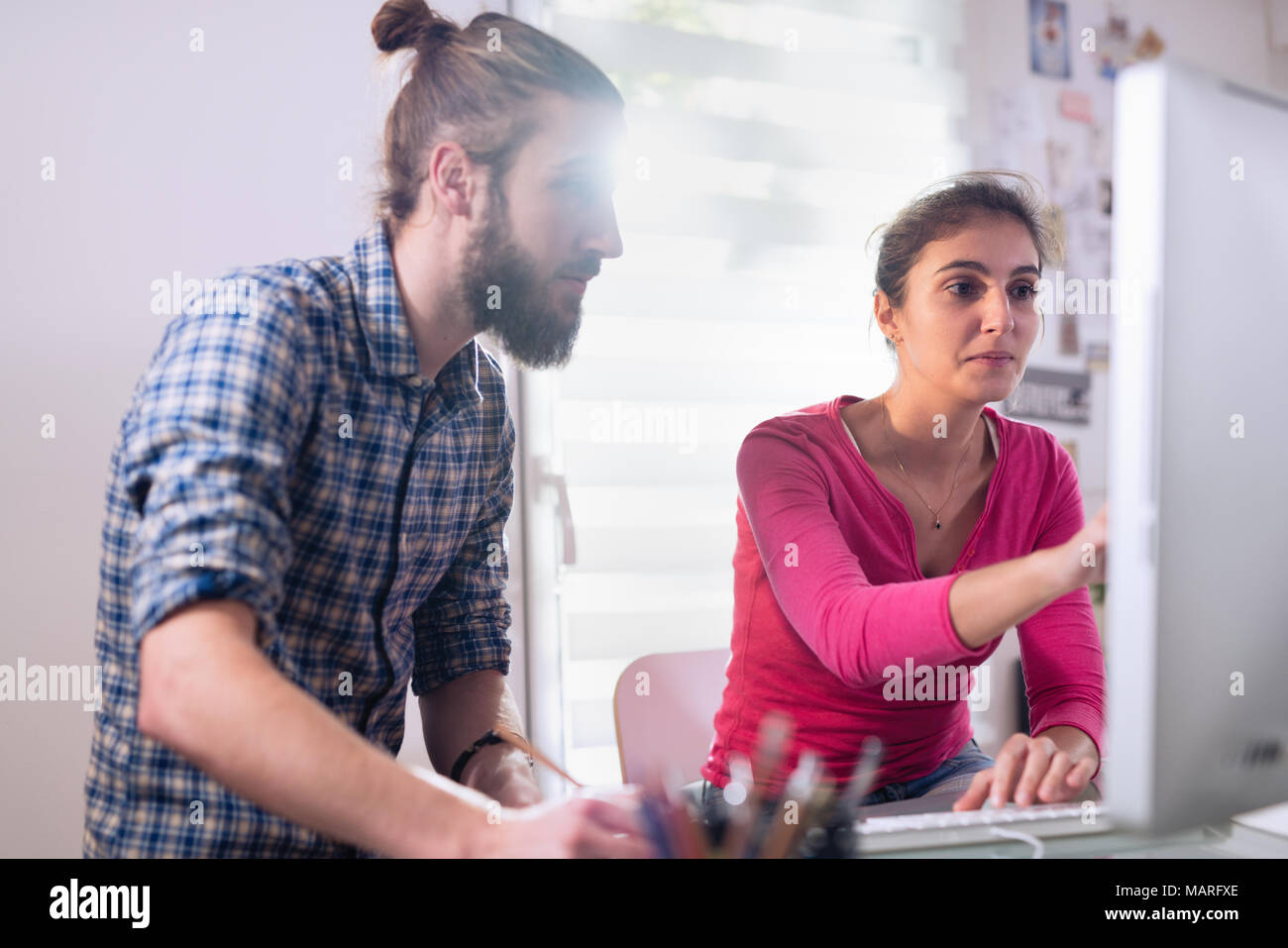 Two colleagues, man and woman sharing ideas about a project - Stock Image