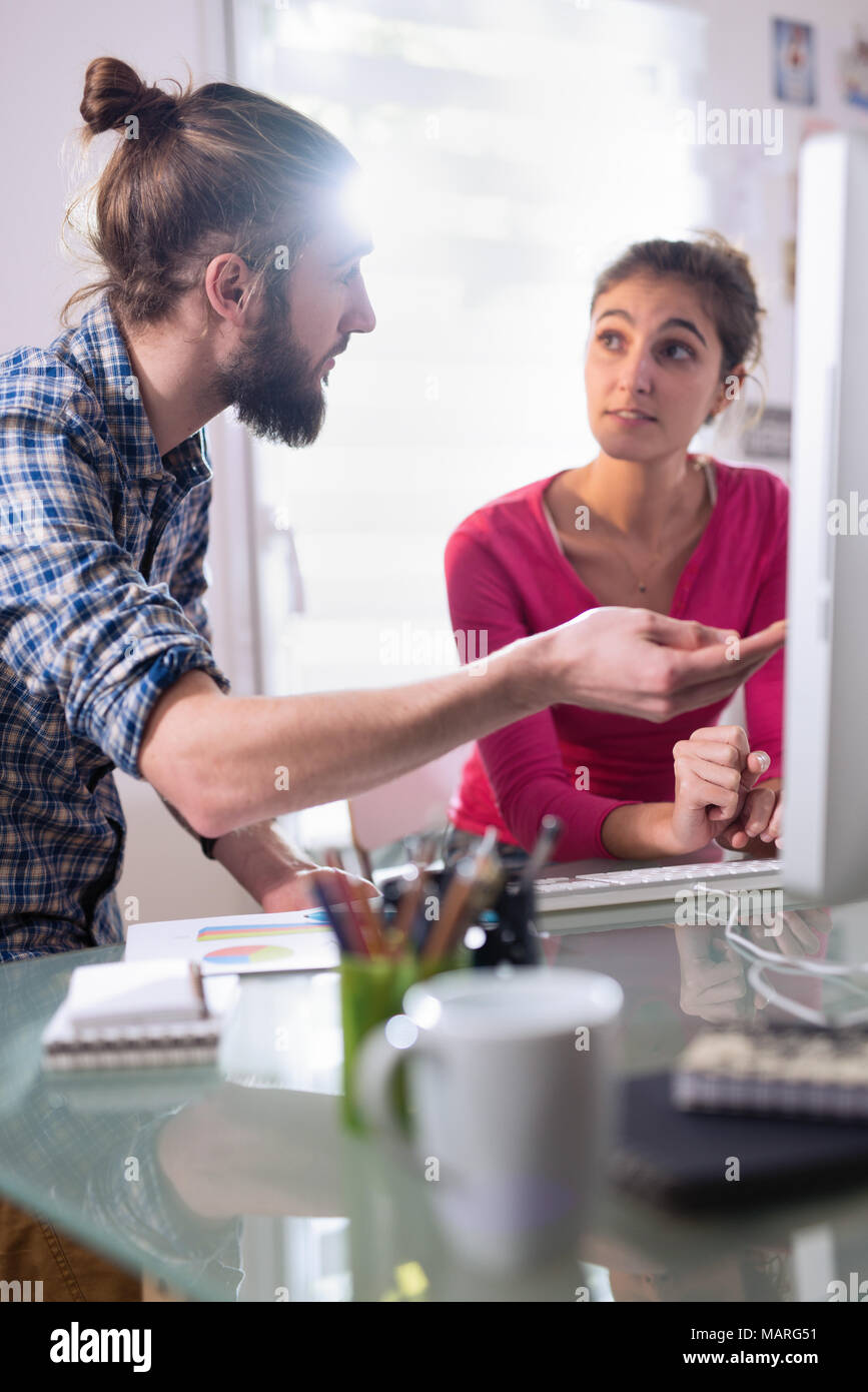 Two students, one man and one woman sharing ideas about project - Stock Image
