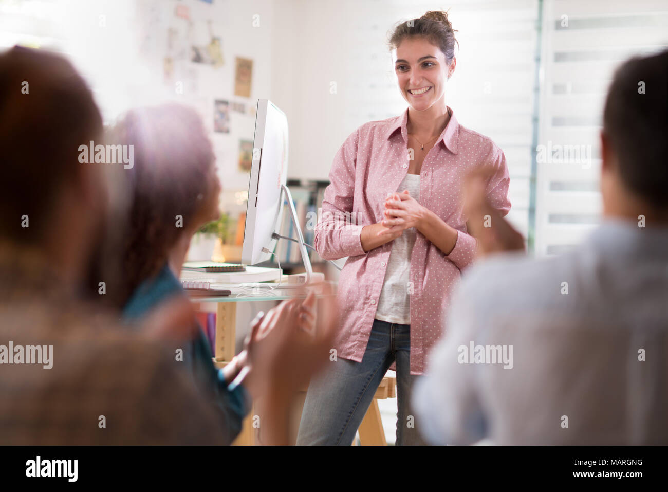 young woman presenting project. she is applauded by colleagues - Stock Image