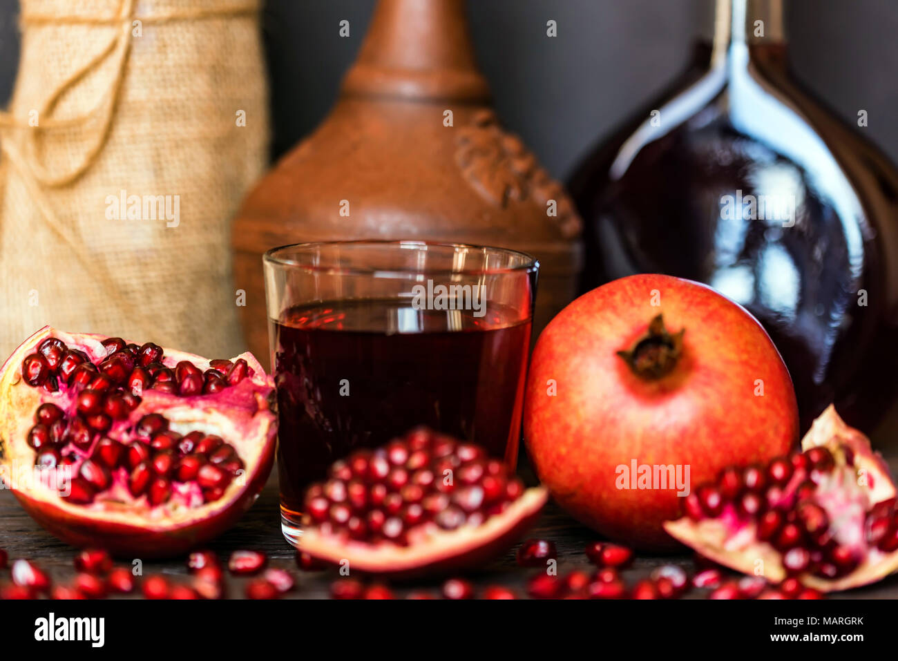 Pomegranate fruit, wine in glass and wine bottles - Stock Image