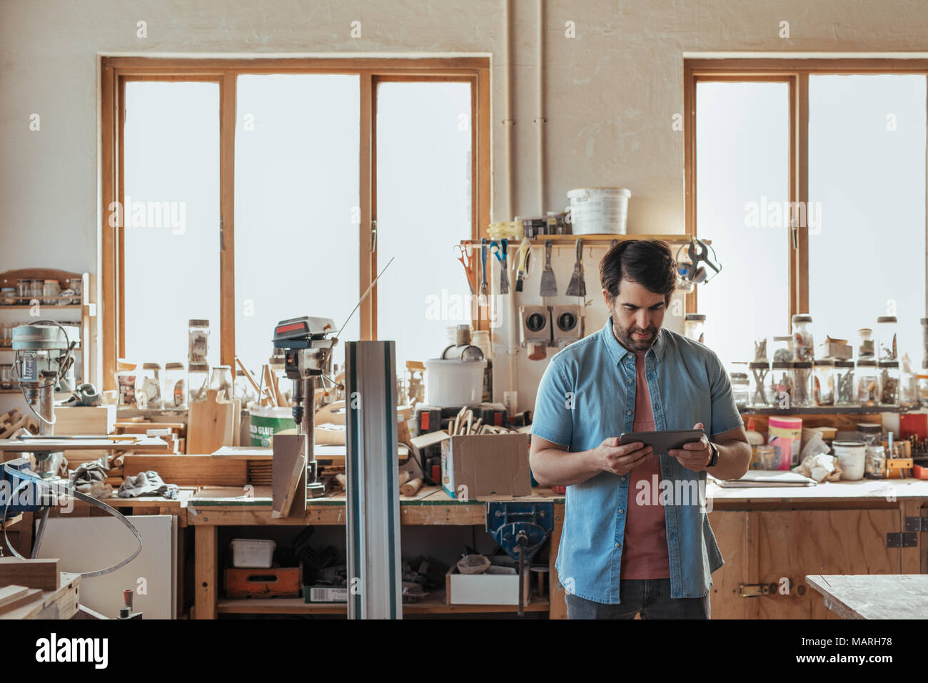 Young carpenter using a digital tablet in his workshop - Stock Image