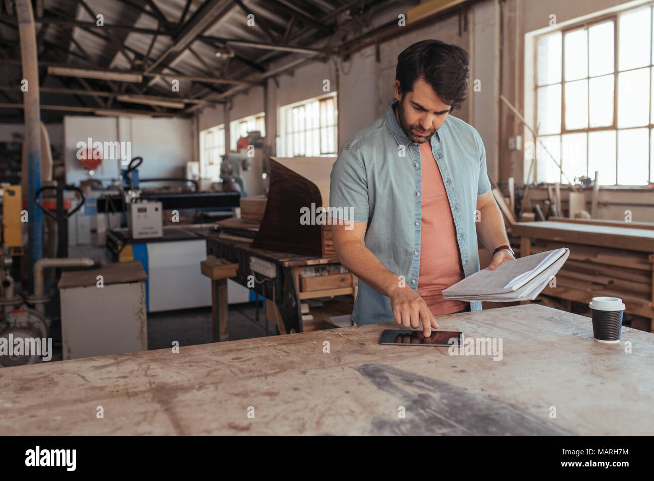 Young woodworker coming up with new designs in his workshop - Stock Image