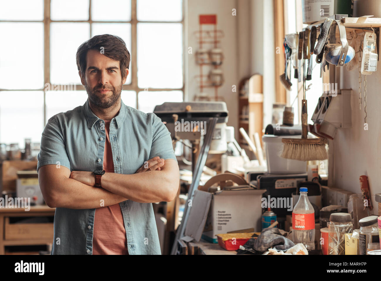 Confident young woodworker standing by a bench in his workshop - Stock Image