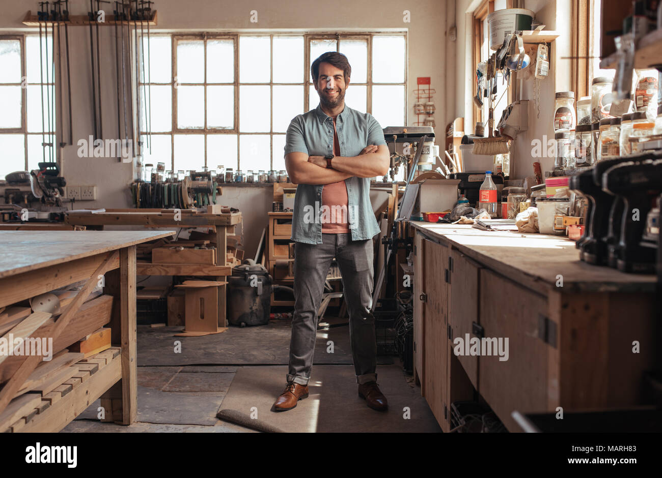 Smiling young woodworker standing in his workshop full of tools - Stock Image