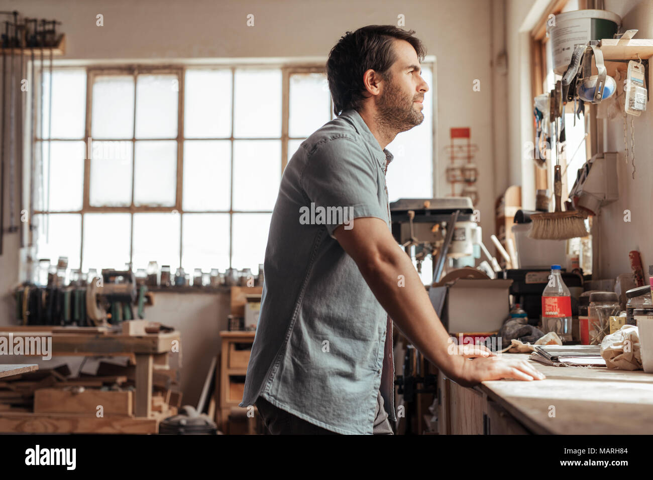 Skilled young woodworker leaning on a workbench deep in thought - Stock Image