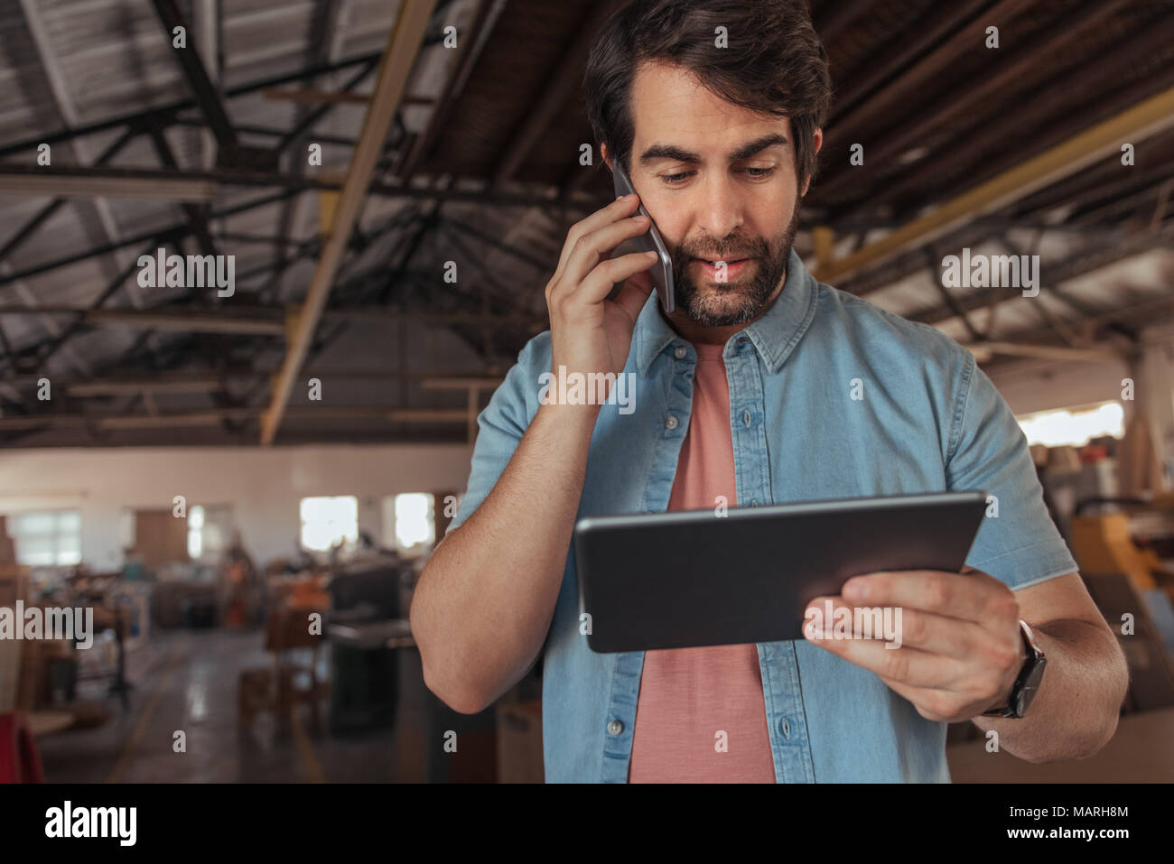 Busy entrepreneur using his tablet while talking on a cellphone - Stock Image
