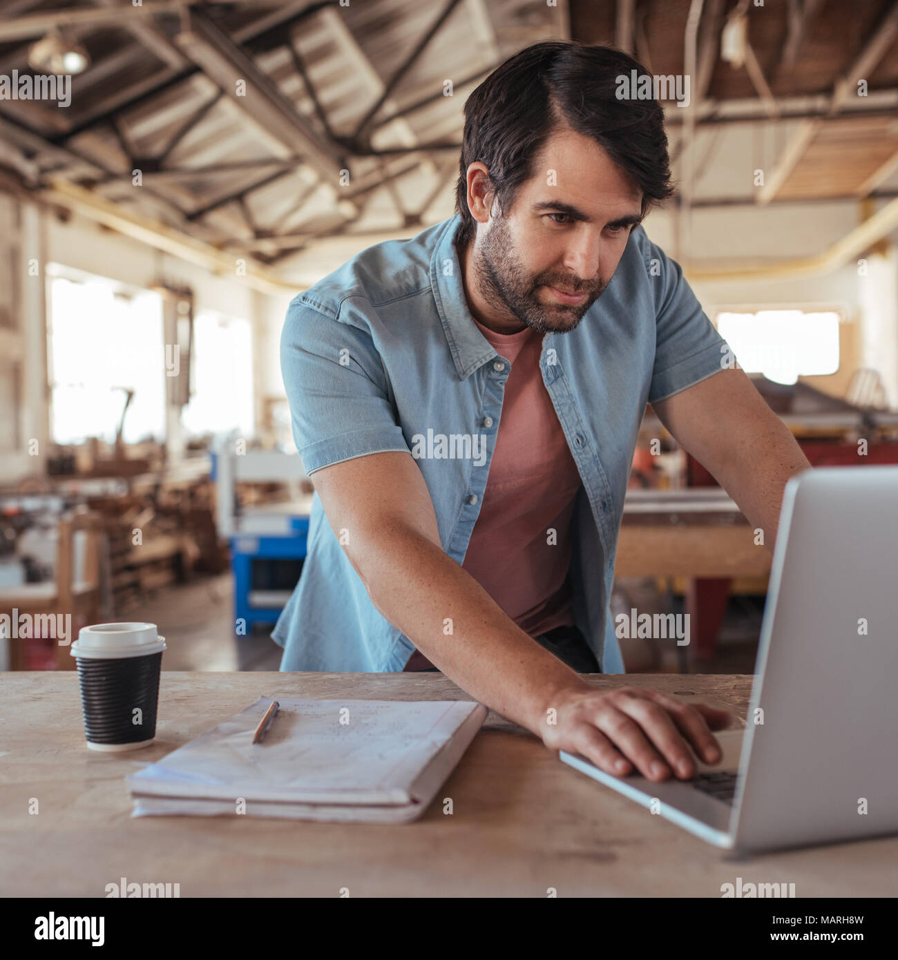 Young woodworker creating new designs on a laptop - Stock Image