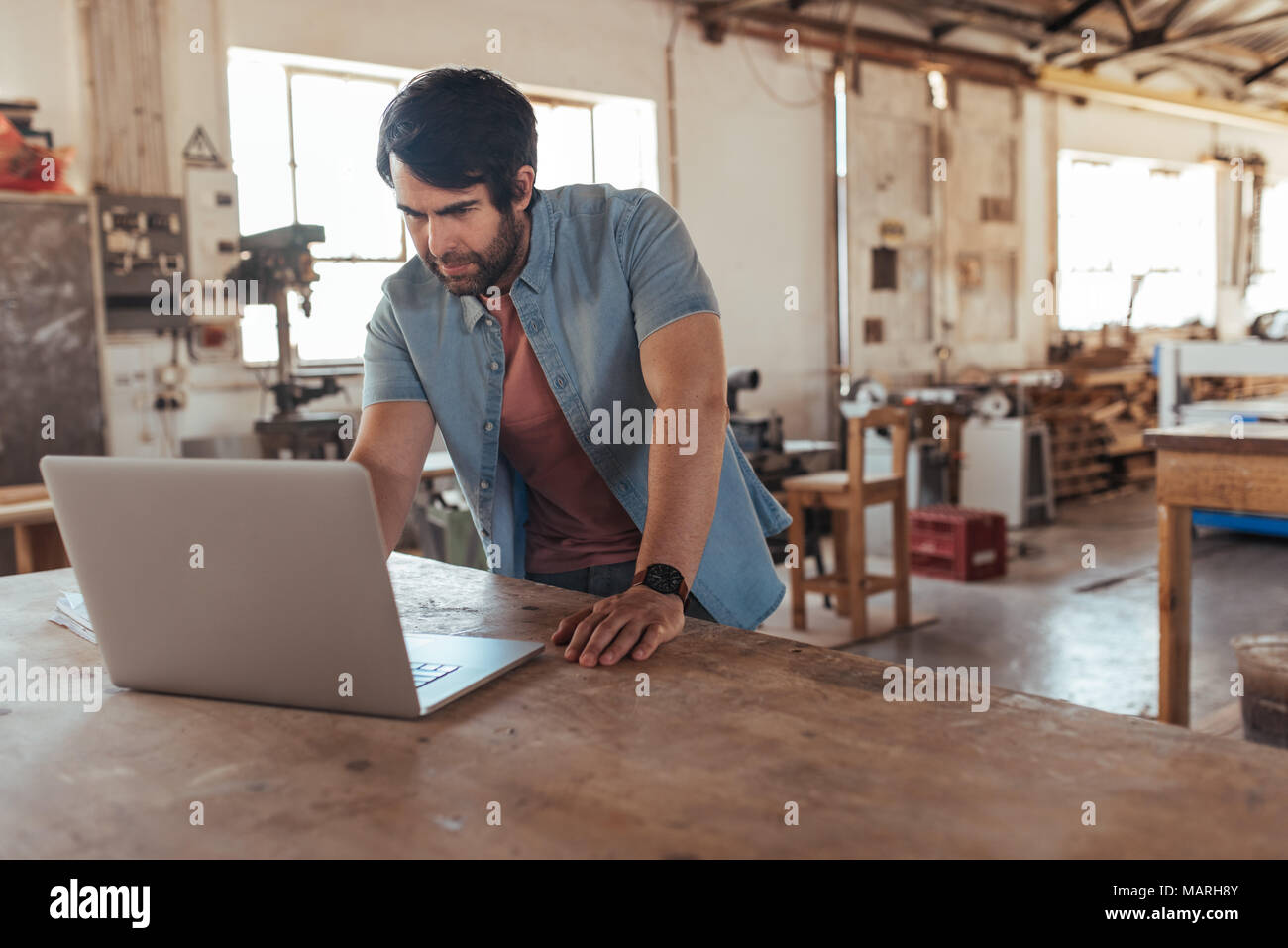 Creative young woodworker creating new designs using a laptop - Stock Image