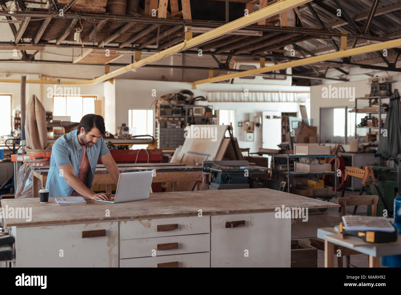 Young woodworker working online at a bench in his workshop - Stock Image