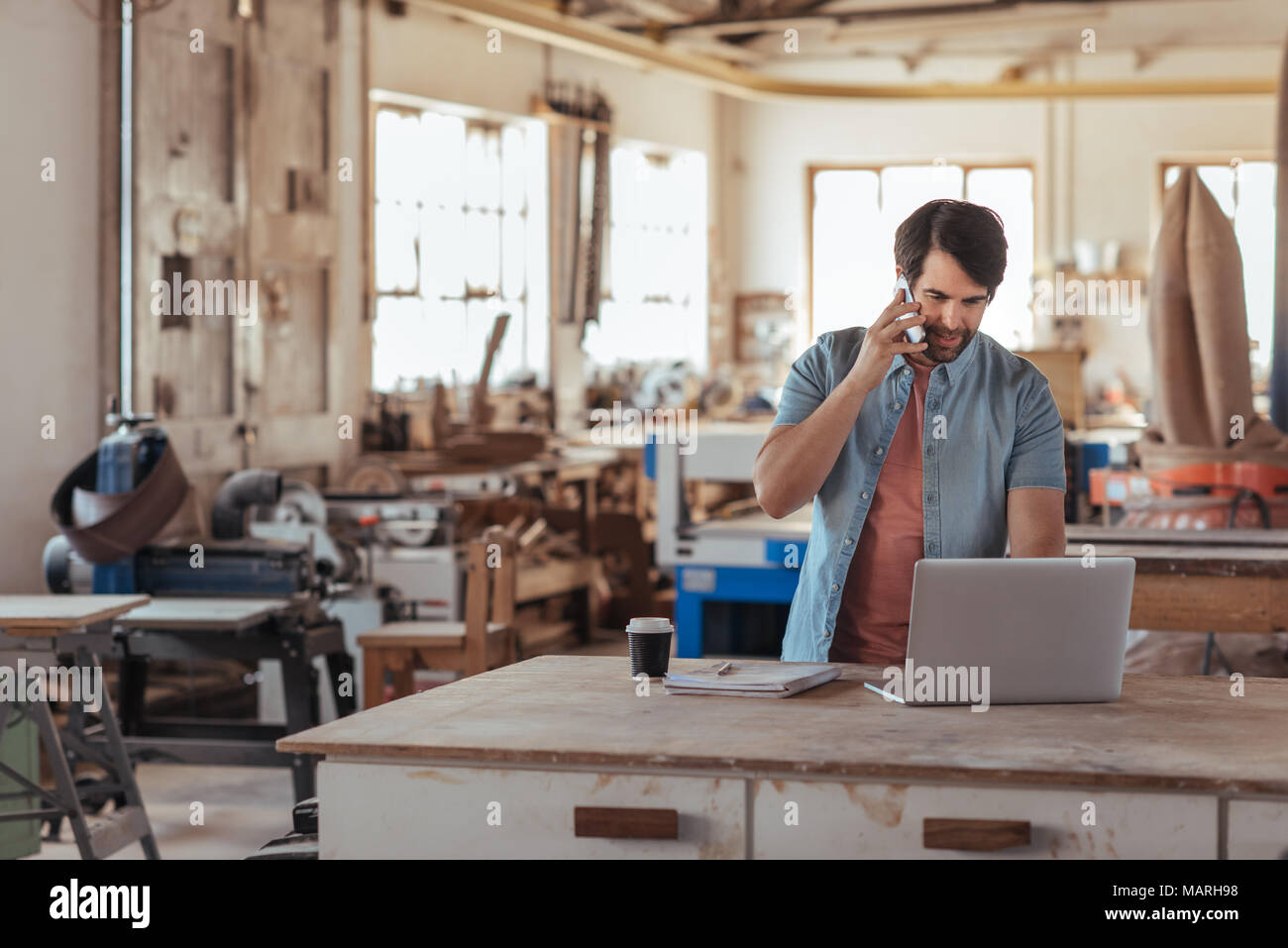 Woodworker using a phone and laptop in his large workshop - Stock Image