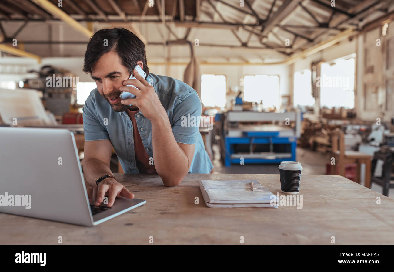Smiling woodworker discussing designs over a cellphone and working online - Stock Image