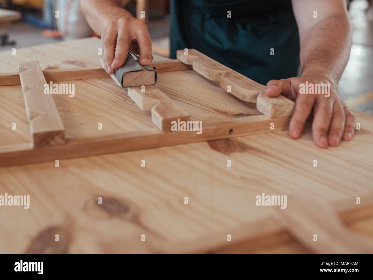 Hands of craftsman sanding a piece of wood in workshop - Stock Image