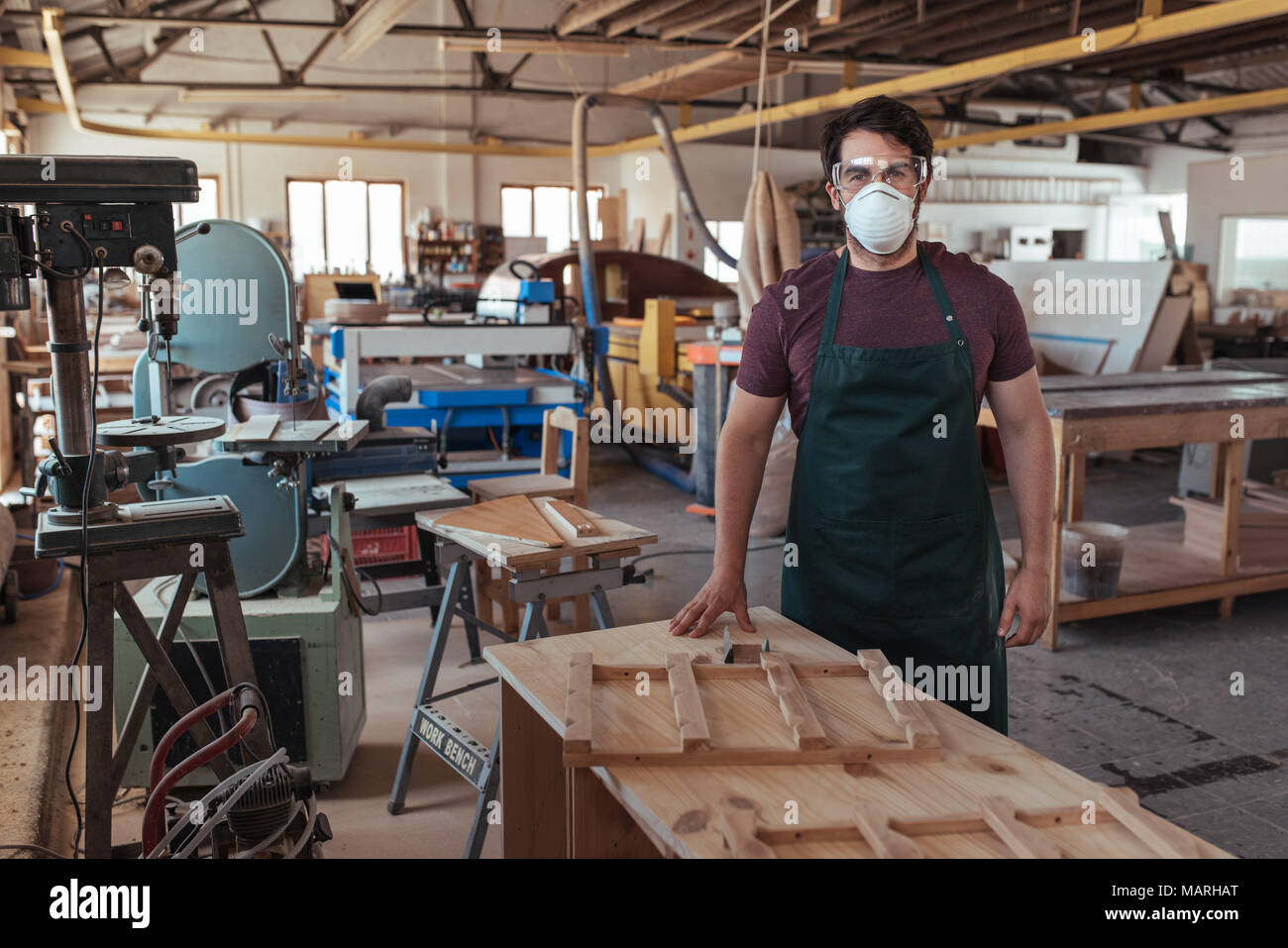 Young woodworker in protective workwear standing in his studio - Stock Image