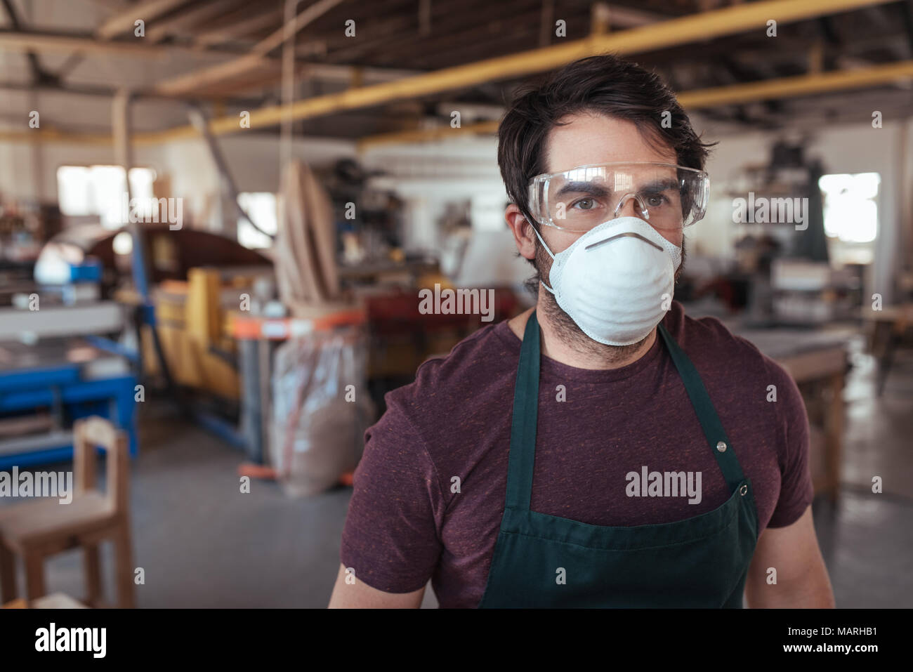 Young woodworker standing alone in his workshop wearing protective gear - Stock Image