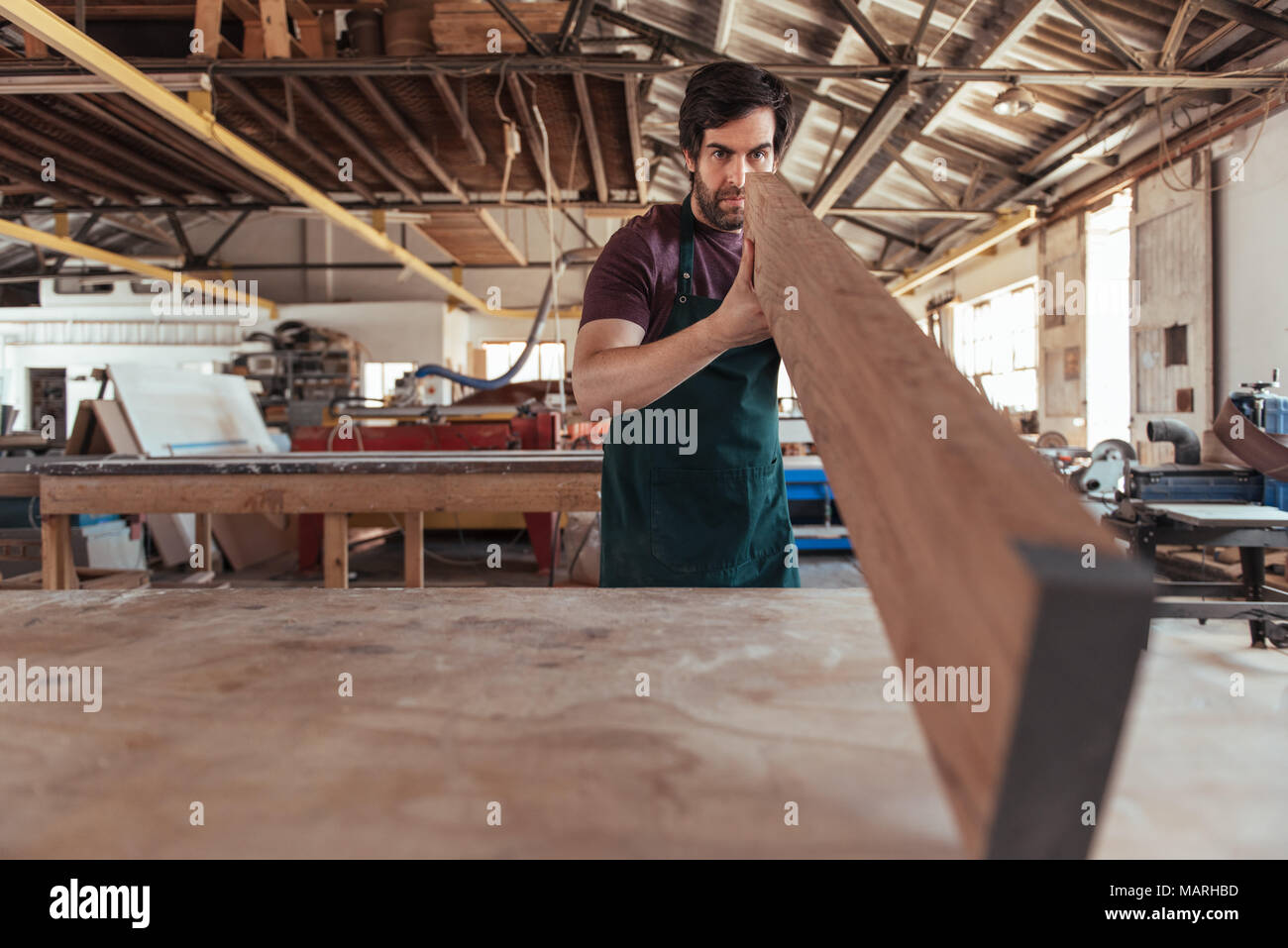Woodworker skillfully inspecting a wooden plank in his workshop - Stock Image