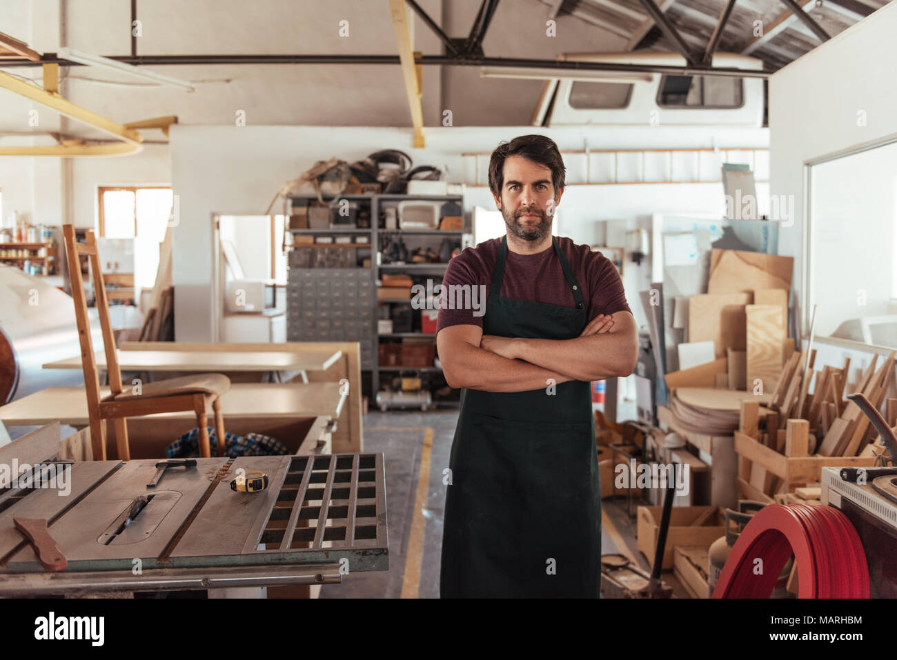 Craftsman standing by a bench saw in his woodworking shop - Stock Image
