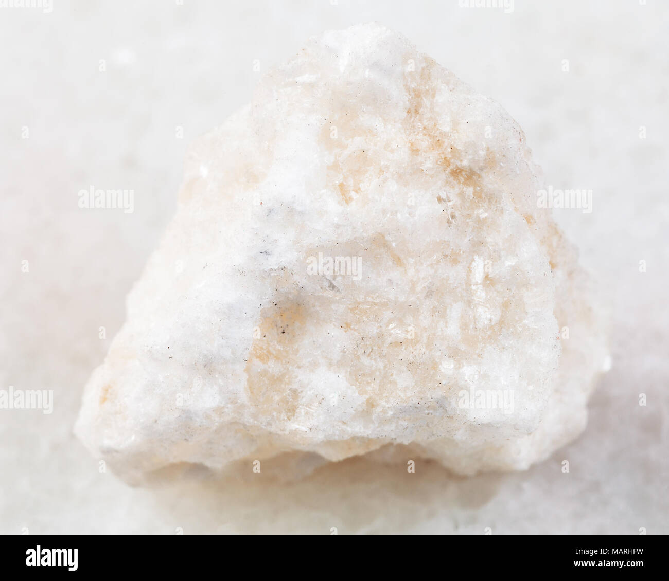 macro shooting of natural mineral rock specimen - rough anhydrite stone on white marble background from Adygea, Russia - Stock Image