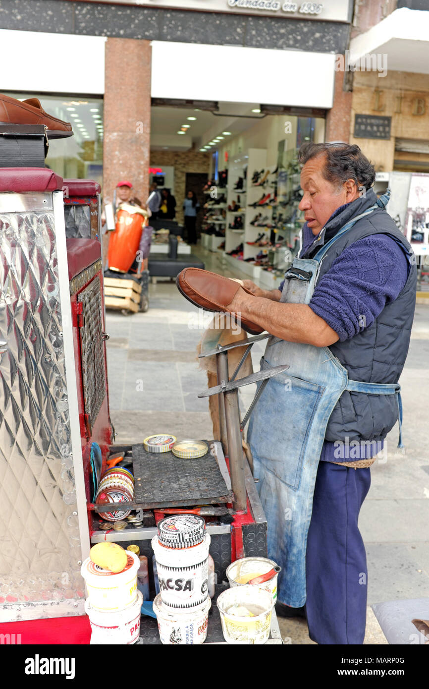 A shoeshine stand on a sidewalk in Mexico City, Mexico, provides and income and occupation for the man shining the shoes. - Stock Image