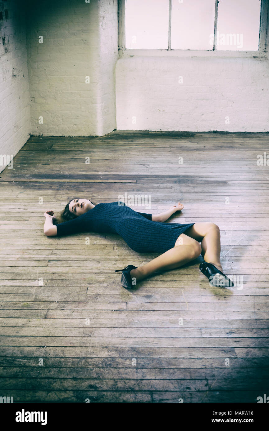 Dead woman laying down on the floor - Stock Image