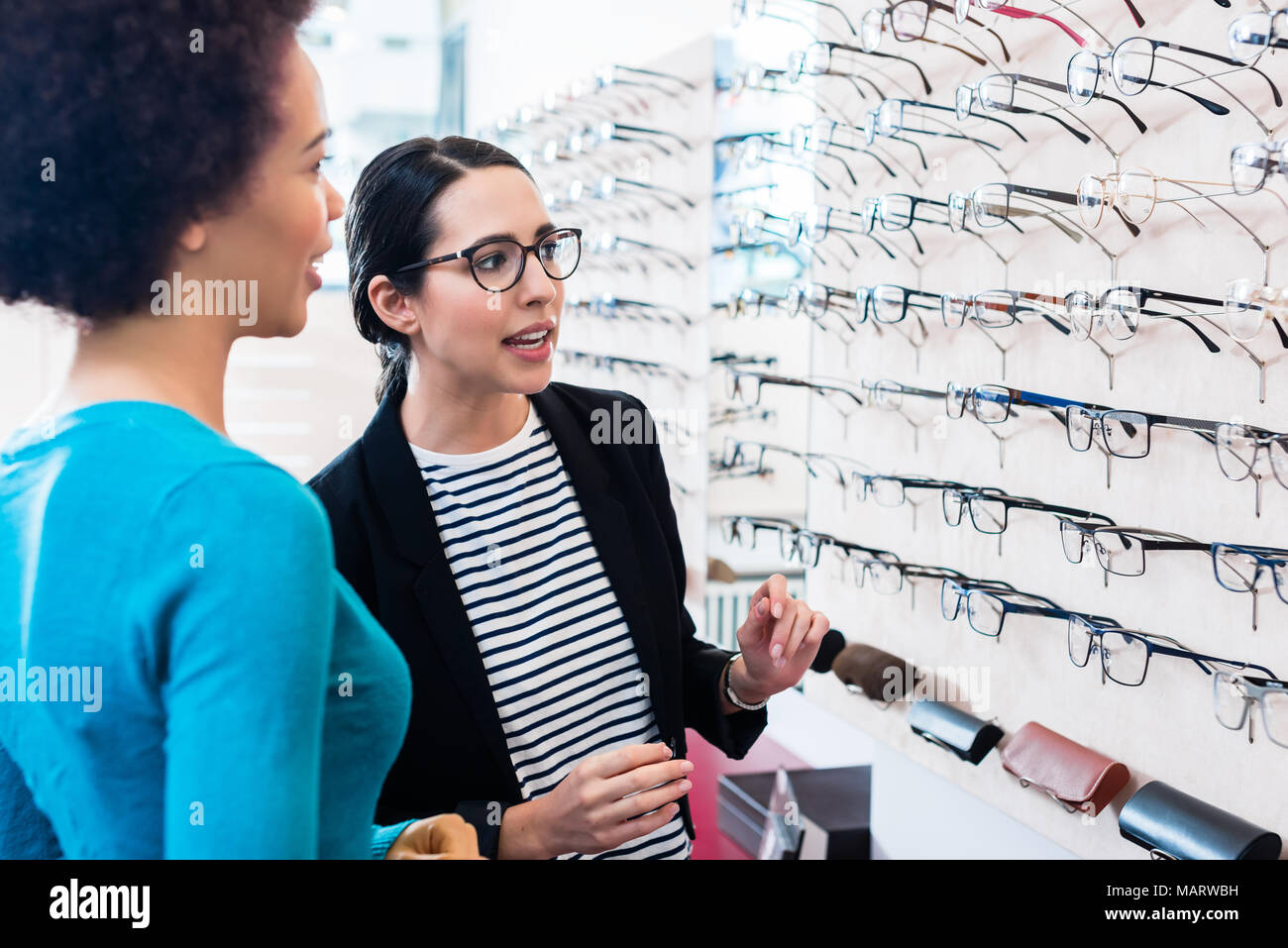 Black woman inspecting glasses in optician shelf - Stock Image