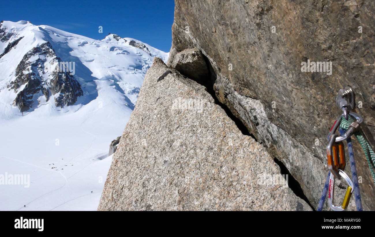 bolt and quick draw with climbing equipment on an exposed and steep climbing route in the French Alps with Mont Blanc in the background Stock Photo