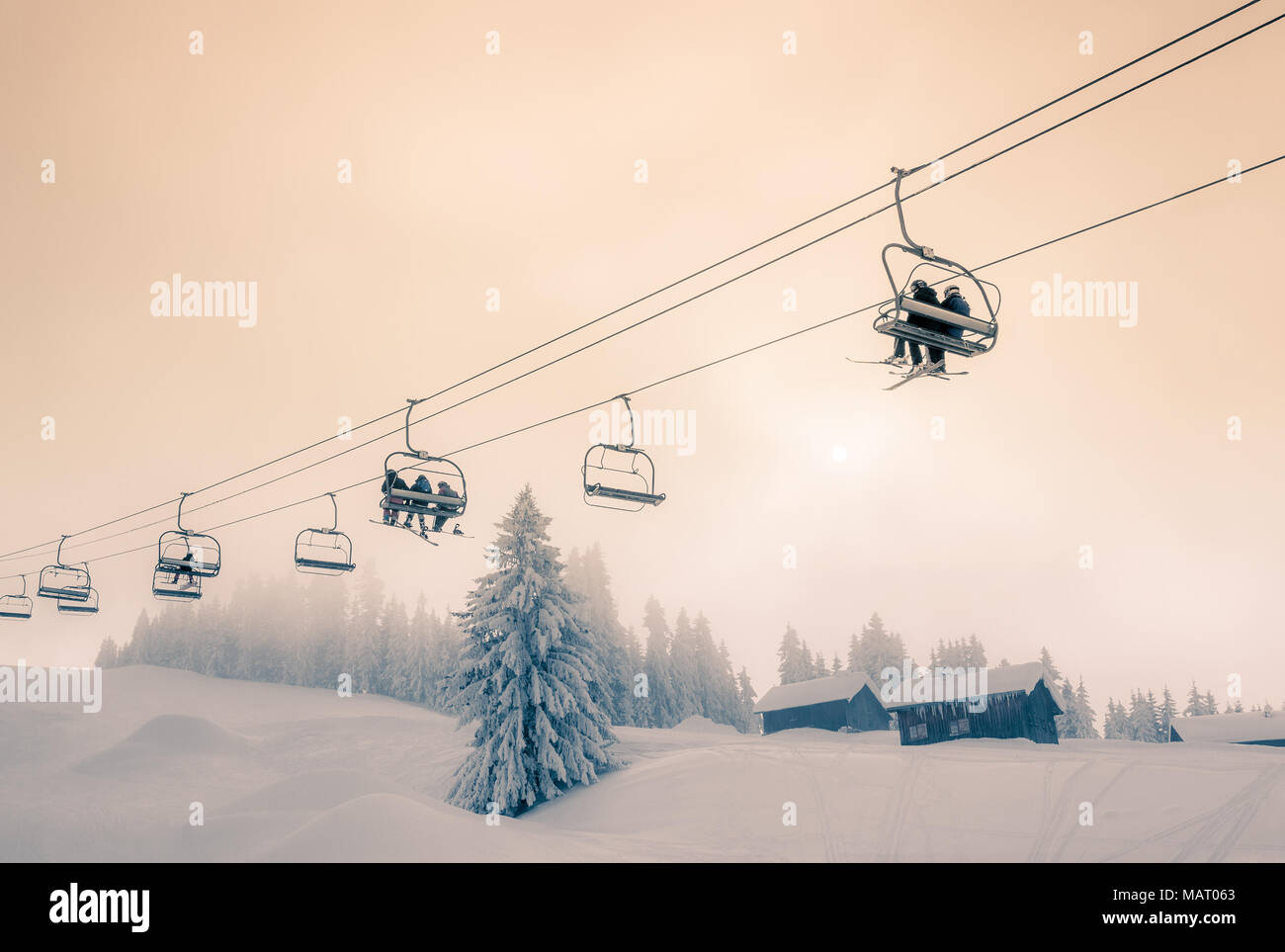 Skiers and Snow Boarders travelling on a chair lift at Morzine Ski Resort in France. Split toned colour treatment. - Stock Image