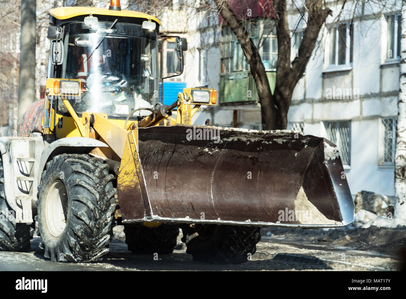 Tractor with snowplow on the street of the city - Stock Image