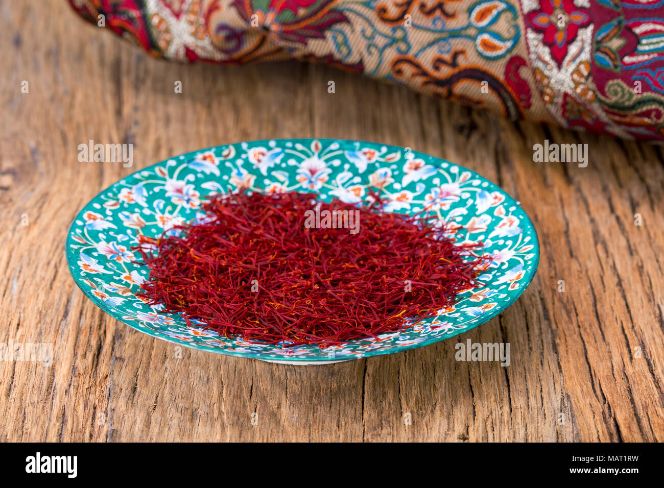 Red Threads And Yellow Style High Grade And Strength Of Dry Saffron Spice On Persian Turquoise Handmade Design Plate On Wooden Table - Stock Image