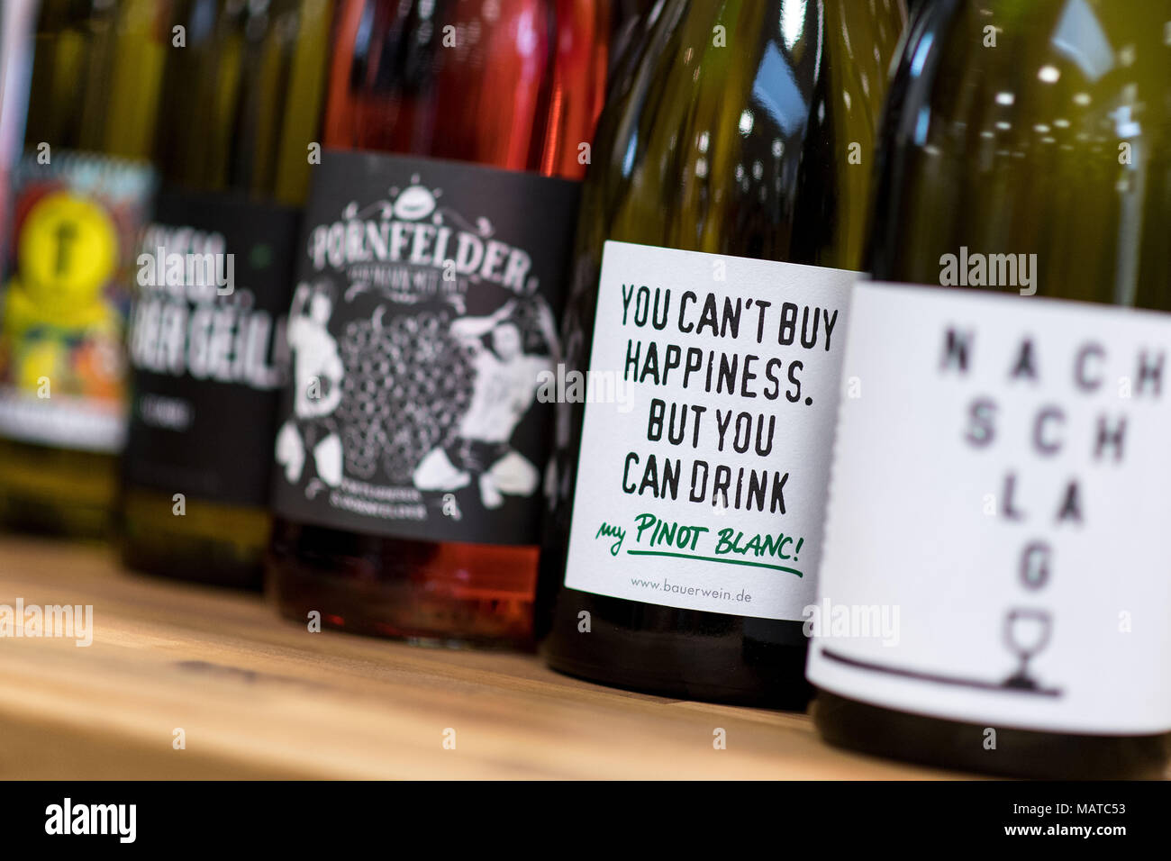 15 March 2018, Germany, Meerbusch: Wines with creatively designed labels and names stand on a table in a wine shop. Photo: Marius Becker/dpa - Stock Image