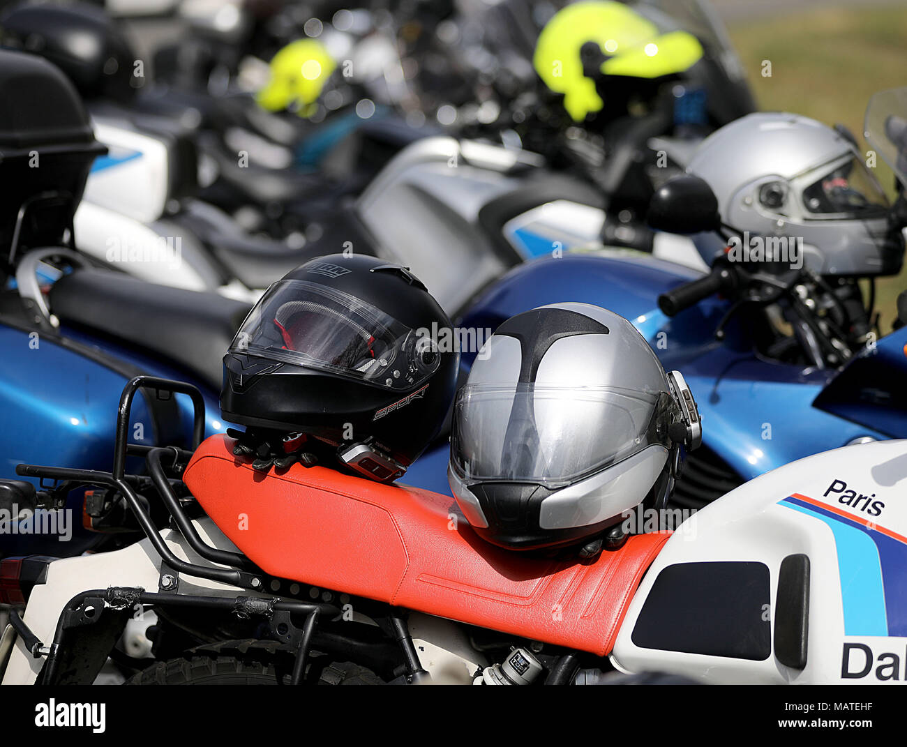 26 March 2018, Germany, Wuppertal: Motor helmets lie on top of motorcycles. North Rhine-Westphalia's Interior Minister Herbert Reul of the Christian Democratic Union (CDU) promotes greater safety measures at the beginning of the motorcycling season. Photo: Oliver Berg/dpa - Stock Image