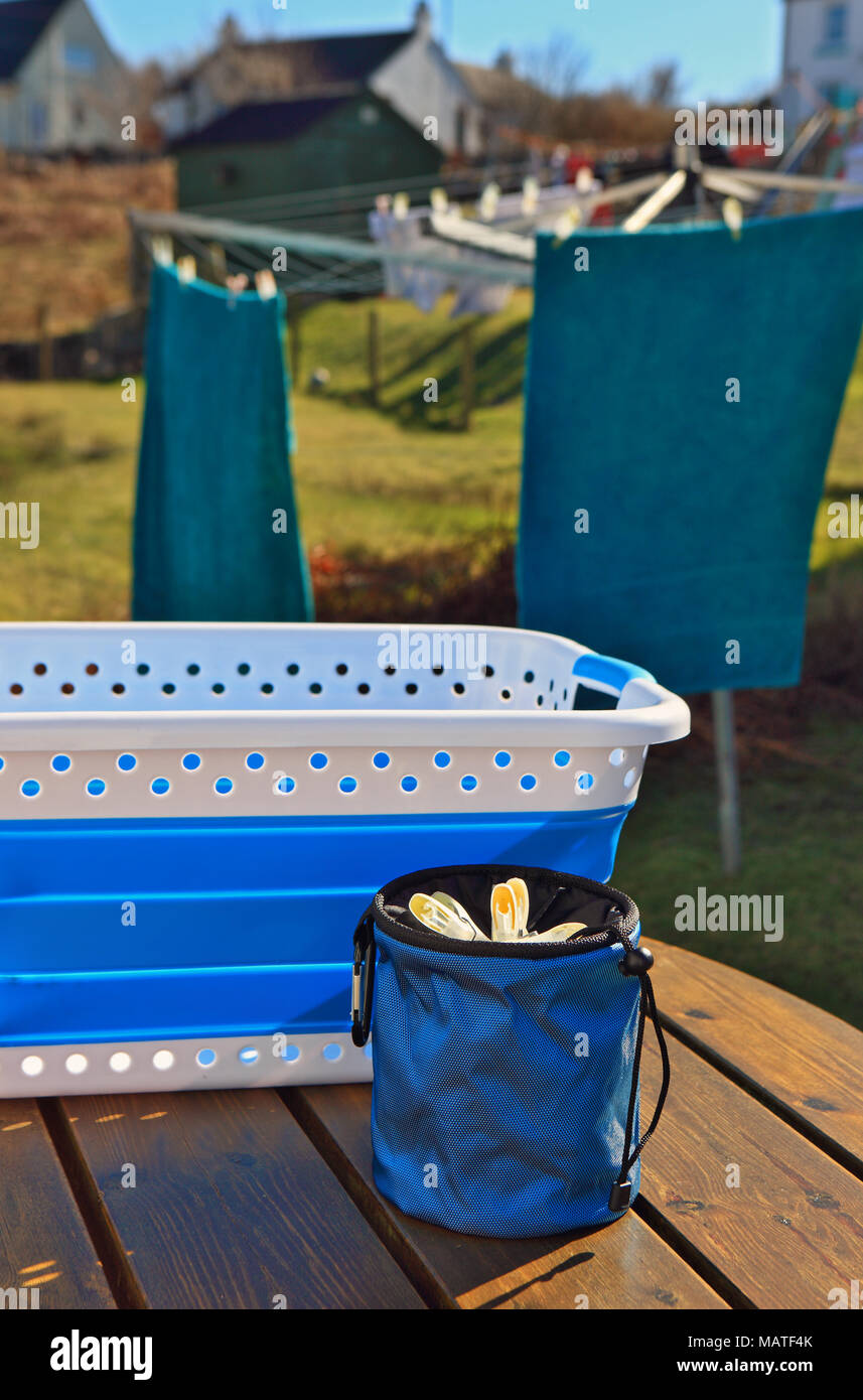 Washing basket and clothes peg basket on a garden bench with washing blowing in the wind in the background - Stock Image